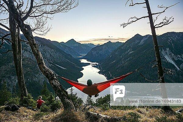 Junger Mann sitzt in einer roten Hängematte  Panoramablick auf Bergkulisse mit See  Sonnenuntergang  Plansee  Tirol  Österreich  Europa