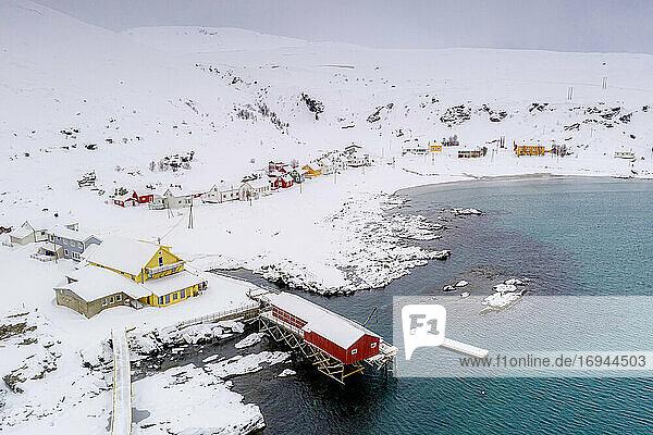 Fischerdorf Sorvaer umrahmt von der kalten See während eines verschneiten Winters  Insel Soroya  Hasvik  Troms og Finnmark  Arktis  Norwegen  Skandinavien  Europa