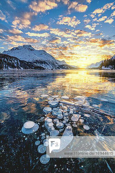 Wolken am brennenden Himmel bei Sonnenuntergang auf dem Piz Da La Margna und Eisblasen  die im Silser See gefangen sind  Engadin  Graubünden  Schweiz  Europa
