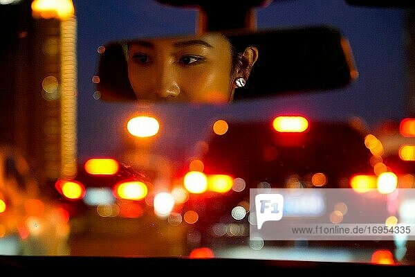 Car rearview mirror display of young women