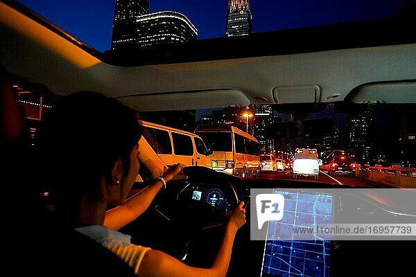 A young woman in traffic at night