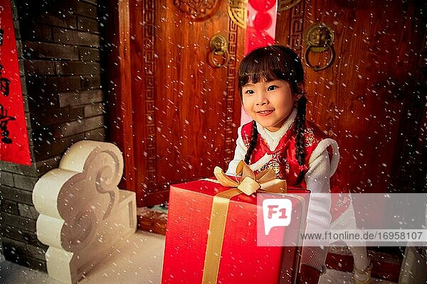 New Year's lovely little girl holding a gift box