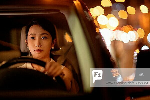 Driving at night confident young woman