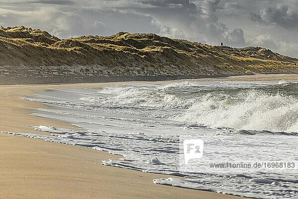 Nordseewellen schlagen an den Strand des Sylter Ellenbogens. Auf der Düne stehen zwei Menschen und schauen über die Nordsee  herbstlich
