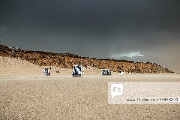 Strandkörbe am menschenleeren Strand von Kampen. Der stürmische Wind hat einen der Körbe umstürzen lassen. Im Hintergrund leuchtet das Rote Kliff in der tiefstehenden Sonne. Darüber wölbt sich ein bleigrauer Wolkenhimmel