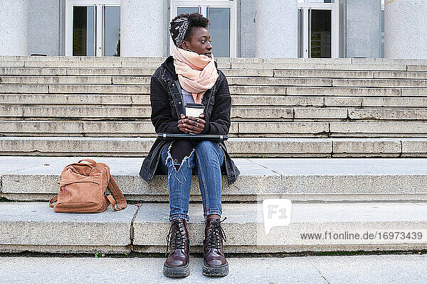Beautiful university female african student looking at side  holding a cup of coffee  sitting on stairs outside on campus. College life concept.