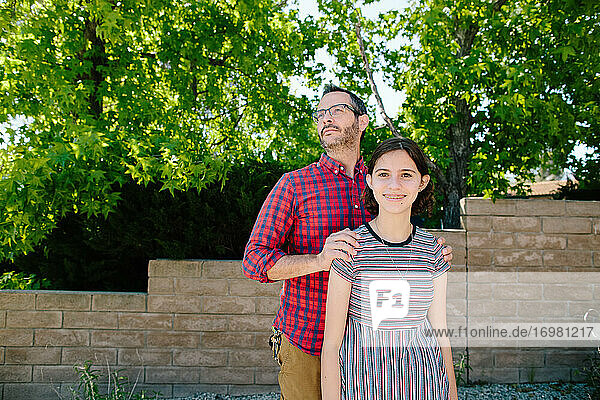 Proud Father With Hands On Her Shoulders Stands Behind Teen Daughter