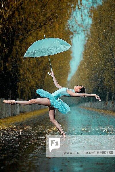 Die junge Frau mit einem Regenschirm tanzen Ballett