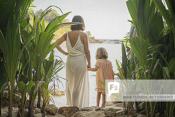 Mother and daughter holding hands on tropical beach  Thailand