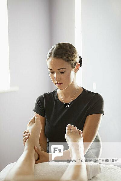 Fokussierte weibliche Masseurin massiert den Fuß des Kunden im Spa