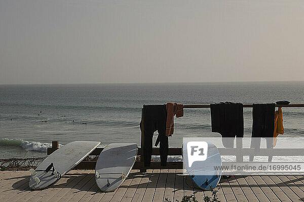 Surfbretter und Neoprenanzüge trocknen an der sonnigen Strandpromenade  Taghazout  Marokko