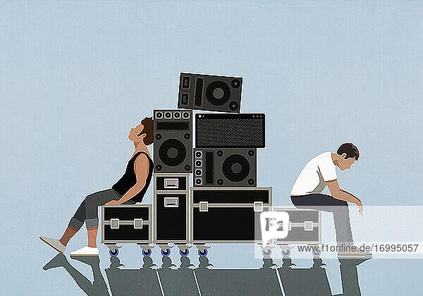 Müde junge Männer  die sich auf Kisten mit Musikgeräten ausruhen