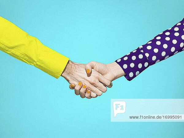 Lebendiger Händedruck auf türkisfarbenem Hintergrund