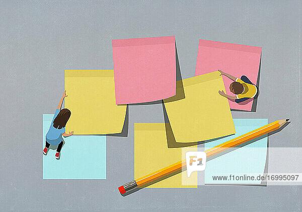 Schulkinder ordnen große mehrfarbige Haftnotizen