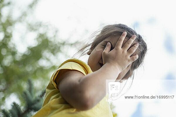 Porträt niedlich  schüchternes Mädchen bedeckt Gesicht mit Hand