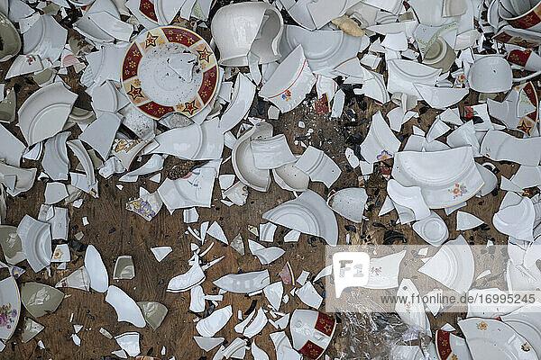 Zerbrochenes Geschirr auf dem Boden verstreut