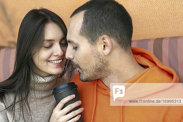 Romantisches junges Paar teilt Kaffee mit Strohhalmen