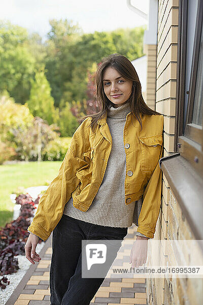 Portrait beautiful young woman in yellow jacket outside house
