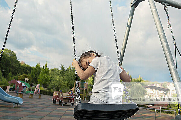Porträt niedlichen Mädchen auf Schaukel im Park Spielplatz