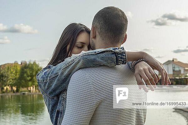Gelassenes  zärtliches junges Paar  das sich am See umarmt
