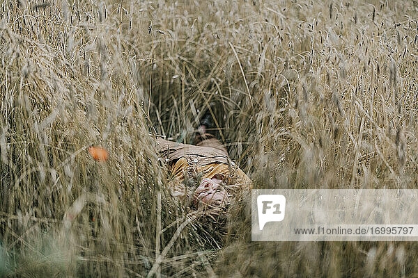Woman relaxing while lying on agricultural field