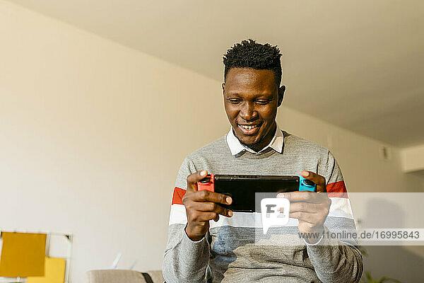 Männlicher Unternehmer  der in seiner Arbeitspause zu Hause ein Videospiel spielt Männlicher Unternehmer, der in seiner Arbeitspause zu Hause ein Videospiel spielt