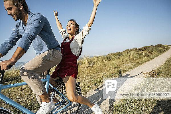 Unbekümmerte Frau genießt Fahrradfahrt mit Mann gegen klaren Himmel Unbekümmerte Frau genießt Fahrradfahrt mit Mann gegen klaren Himmel