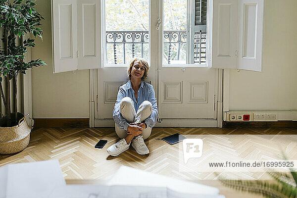 Nachdenkliche Geschäftsfrau sitzt auf dem Boden vor dem Fenster im Büro