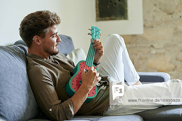 Young man playing ukulele on sofa in living room at home