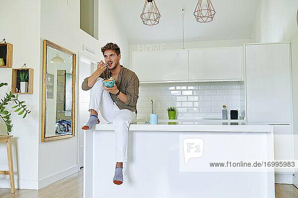 Junger Mann isst Salat  während er über dem Tresen in der Küche sitzt Junger Mann isst Salat, während er über dem Tresen in der Küche sitzt