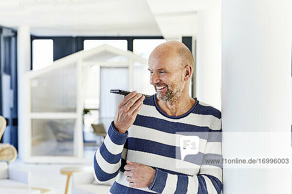 Smiling man talking on mobile phone while standing at home