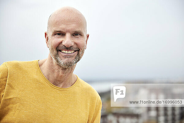 Smiling man standing on rooftop