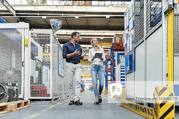 Weibliche und männliche Kollegen diskutieren beim Gehen in einer Fabrik