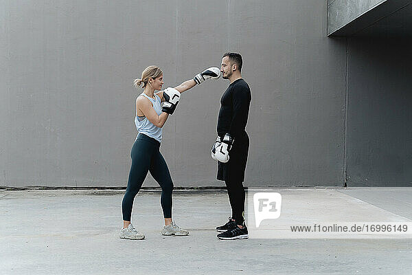 Female athlete punching man while practicing against wall