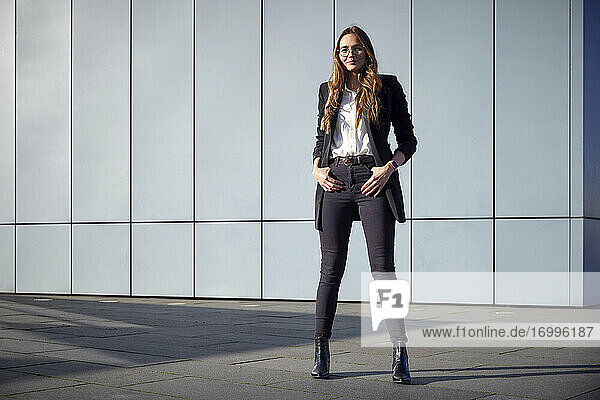 Young businesswoman with hands in pockets standing on footpath