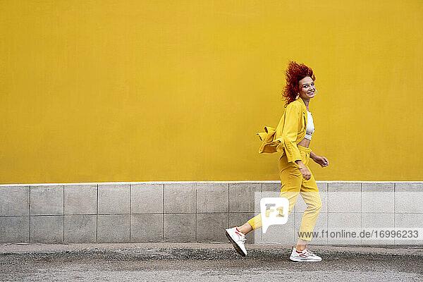 Energetische junge Frau in gelbem Anzug läuft und springt vor einer gelben Wand Energetische junge Frau in gelbem Anzug läuft und springt vor einer gelben Wand