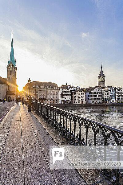 Switzerland  Canton of Zurich  Zurich  Minster Bridge at sunset with riverside buildings in background