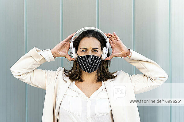 Female entrepreneur listening music through headphones against glass wall during COVID-19