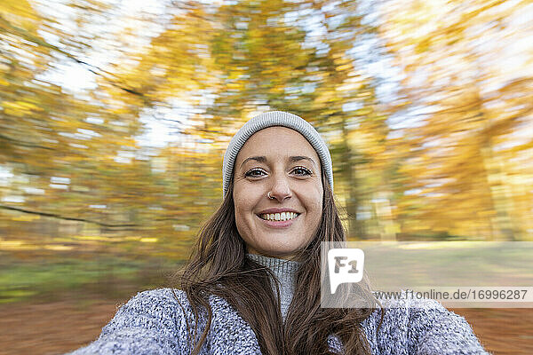 Smiling female hiker standing in Cannock Chase woodland during autumn