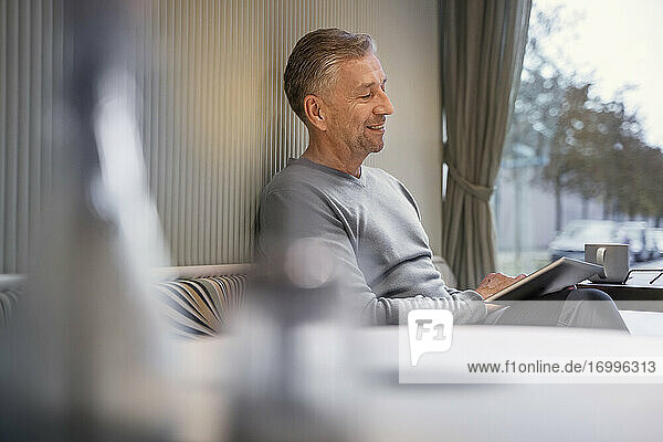 Smiling businessman using digital tablet while sitting at modern cafe