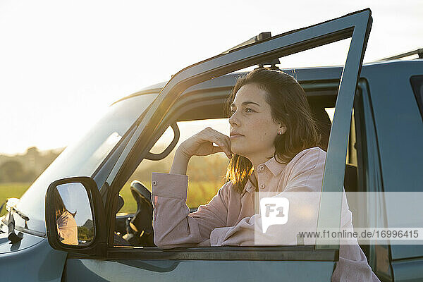 Thoughtful young woman leaning on car door during sunset