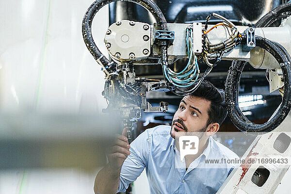 Male entrepreneur concentrating while analyzing machine part in manufacturing factory
