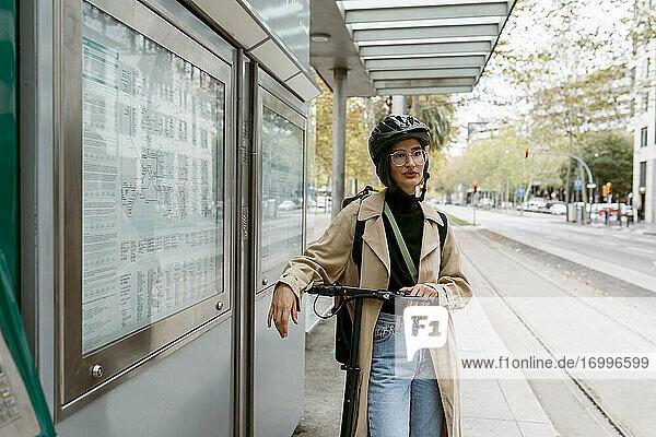 Frau mit Fahrradhelm steht mit elektrischem Roller an einer Straßenbahnhaltestelle in der Stadt Frau mit Fahrradhelm steht mit elektrischem Roller an einer Straßenbahnhaltestelle in der Stadt