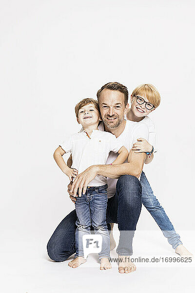 Happy father with sons against white background