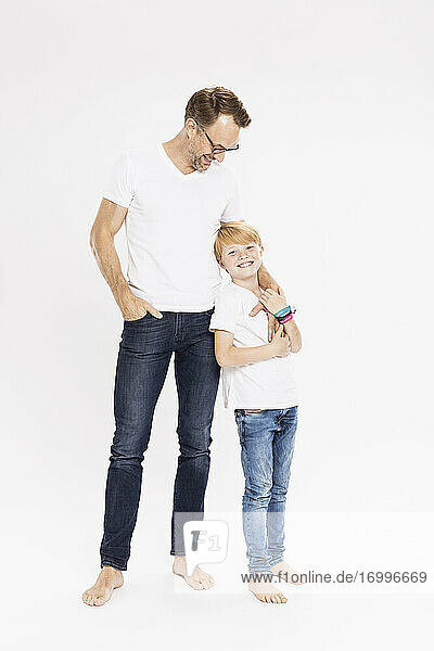 Smiling father looking at son while standing against white background