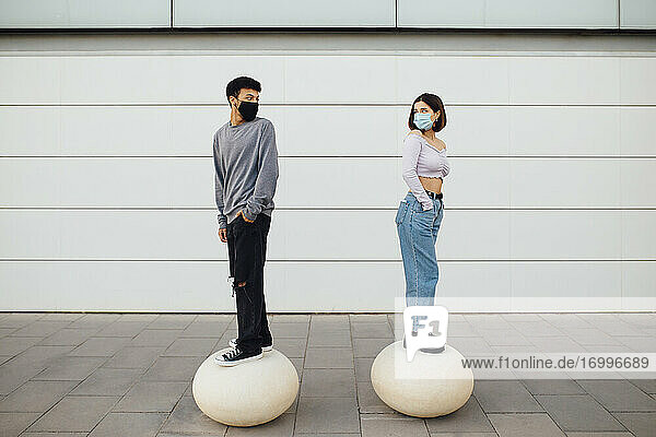 Couple with face mask looking over shoulder while standing on white concrete ball