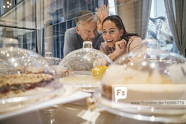 Smiling businesswoman looking at cake display while standing by man at modern cafe