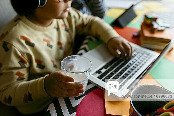 Junge hält ein Glas Milch in der Hand  während er zu Hause am Laptop sitzt Junge hält ein Glas Milch in der Hand, während er zu Hause am Laptop sitzt