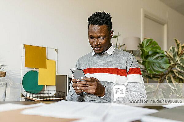 Geschäftsmann  der bei der Arbeit von zu Hause aus Textnachrichten auf seinem Smartphone verschickt Geschäftsmann, der bei der Arbeit von zu Hause aus Textnachrichten auf seinem Smartphone verschickt