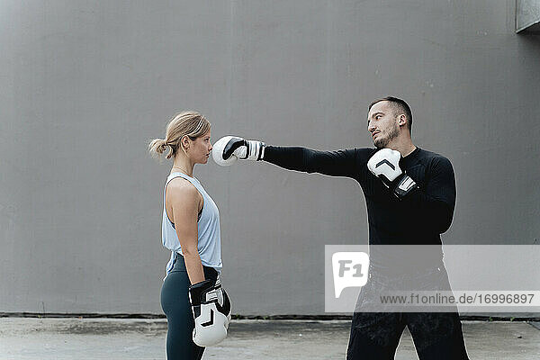 Sportsman teaching boxing to woman while standing against wall